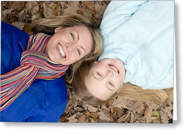 Mother And Daughter On Autumn Leaves Greeting Card by Ian Boddy