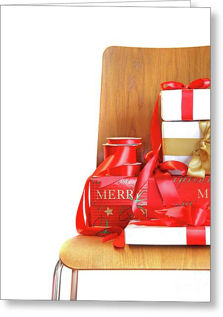 Pile Of Gifts On Wooden Chair Against White Greeting Card by Sandra Cunningham