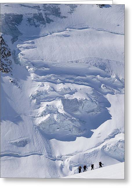 Skiers Cross The Aletsch Glacier En Greeting Card by Axiom Photographic