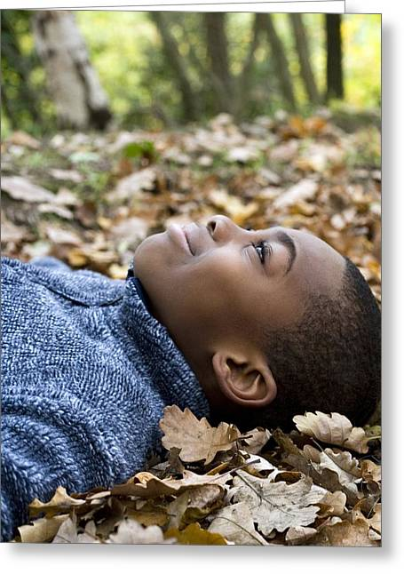 Smiling Boy Lying On Autumn Leaves Greeting Card