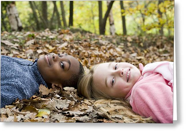 Smiling Children Lying On Autumn Leaves Greeting Card by Ian Boddy