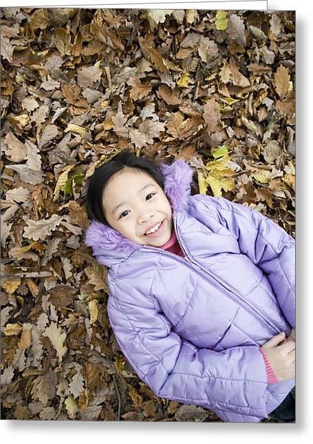 Smiling Girl Lying On Autumn Leaves Greeting Card