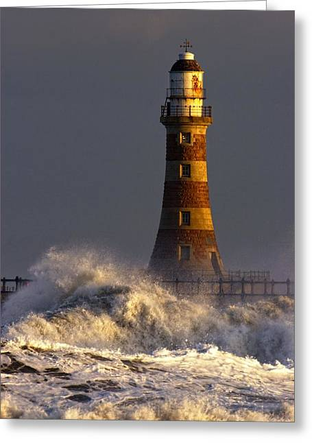 Waves Crashing Against A Lighthouse Greeting Card by John Short
