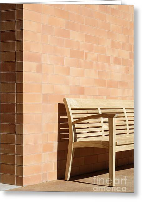 Wooden Bench Against Corner Of Brick Building Greeting Card by Jeremy Woodhouse
