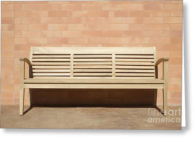 Wooden Bench Set Against Brick Wall Greeting Card by Jeremy Woodhouse
