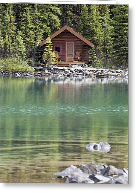 Wooden Cabin Along A Lake Shore Greeting Card by Michael Interisano