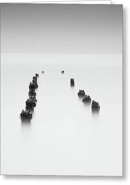Greeting Card featuring the photograph Damaged Wooden Poles Of An Old Pier In The Ocean. by Michalakis Ppalis
