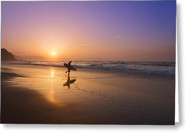 Surfer Entering Water At Sunset Greeting Card by Mikel Martinez de Osaba