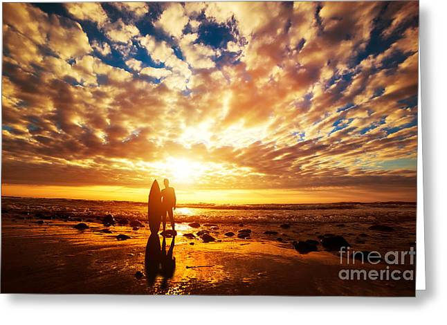 Surfer Standing With His Surfboard On The Beach At Sunset Over The Ocean Greeting Card