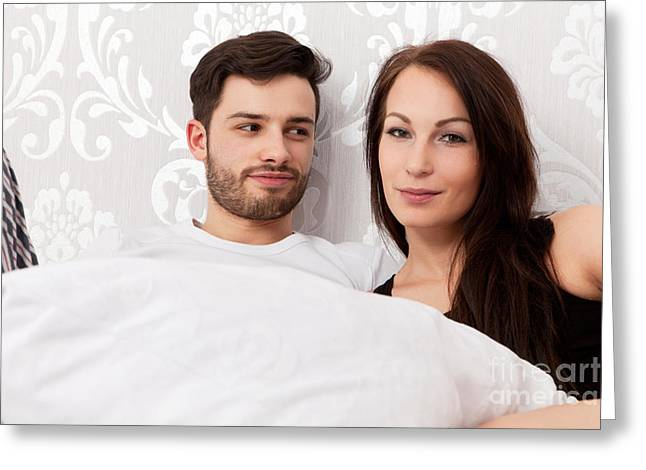 Young Couple Snuggling In Bed Greeting Card