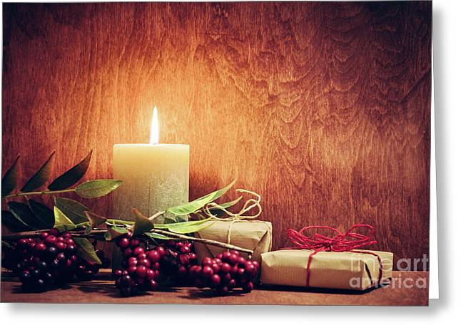 Chistmas Presents, Gifts With A Candle Glowing On Wooden Wall Background. Greeting Card by Michal Bednarek