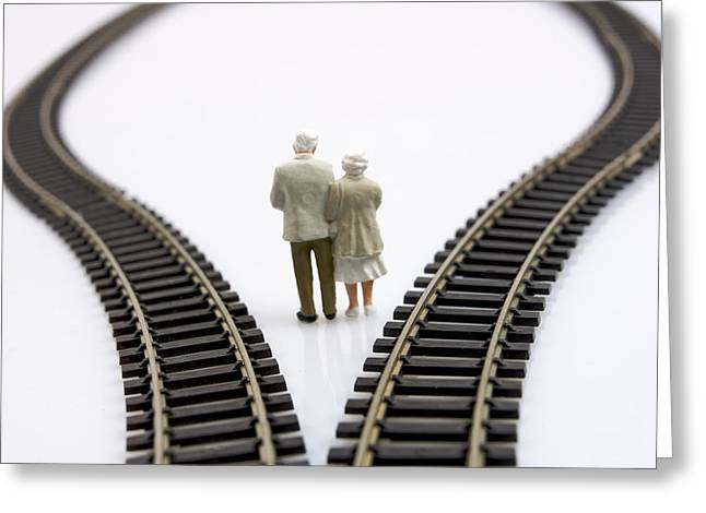 Figurines Between Two Tracks Leading Into Different Directions Symbolic Image For Making Decisions. Greeting Card