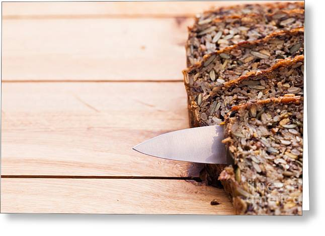 Knife In Wholemeal Bread On Wooden Table Greeting Card by Michal Bednarek