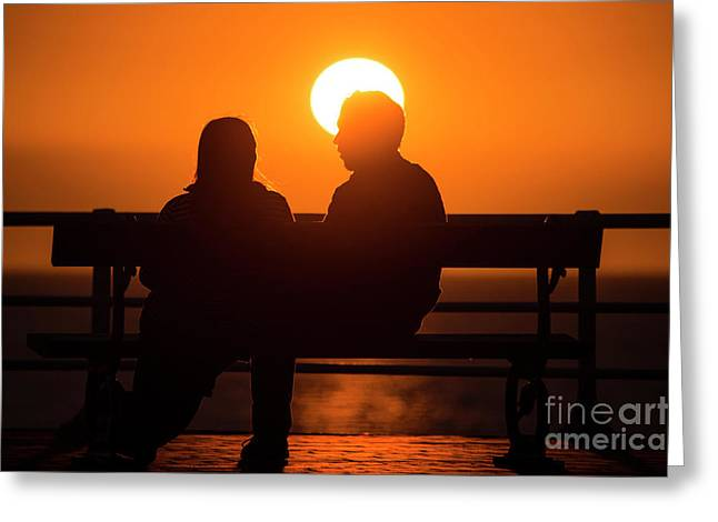 A Couple Sitting At Sunset Greeting Card