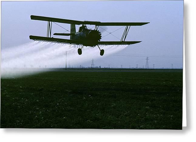 A Crop Duster Flies Over A Field Greeting Card by Kenneth Garrett
