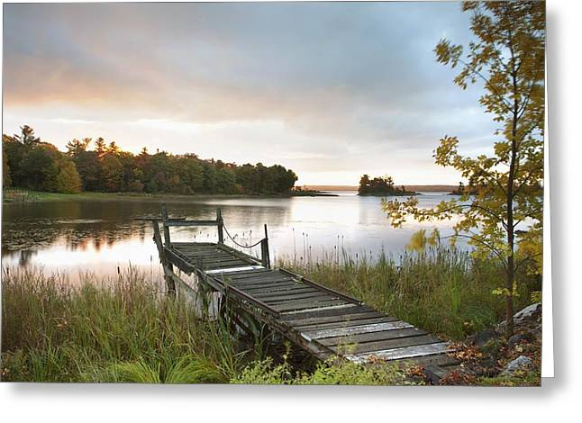 Sunrise. Water Greeting Cards - A Dock On A Lake At Sunrise Near Wawa Greeting Card by Susan Dykstra