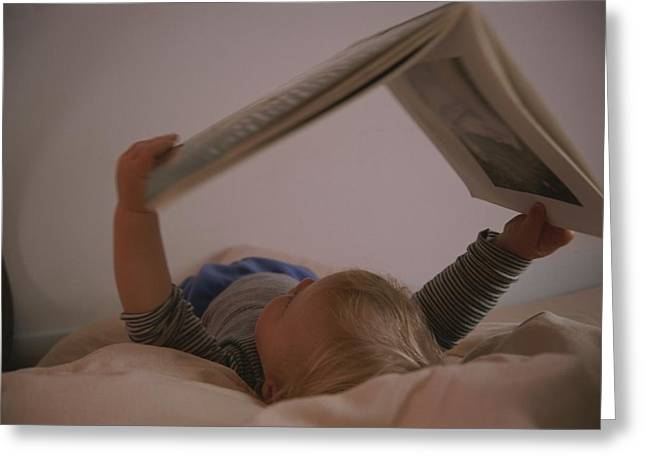 National Children Greeting Cards - A Toddler Looks At A Book While Lying Greeting Card by Roy Gumpel