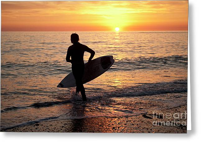 A Young Man Surfing At Sunset Off Aberystwyth Beach, Wales Uk Greeting Card
