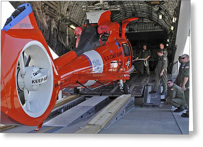 An Aircrew Loads A Coast Guard Hh-65 Greeting Card by Stocktrek Images