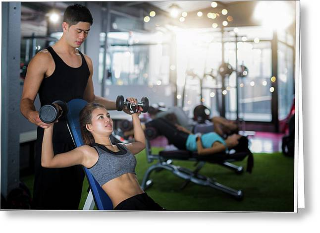 Asian Trainer And Lady Take Personal Training In Fitness Club Greeting Card