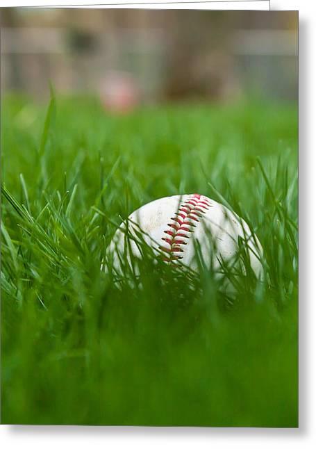 Baseball In Grass Greeting Card by Erin Cadigan