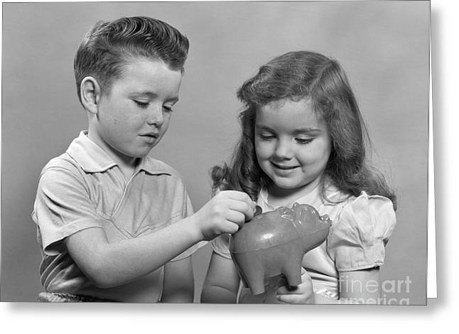 Boy And Girl Putting Money Into Piggy Greeting Card by H. Armstrong Roberts/ClassicStock