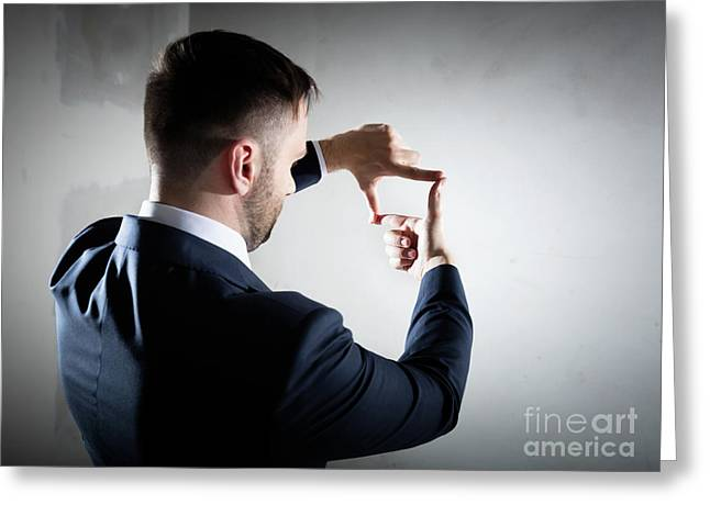 Businessman Framing His Hands On Empty Concrete Wall Greeting Card