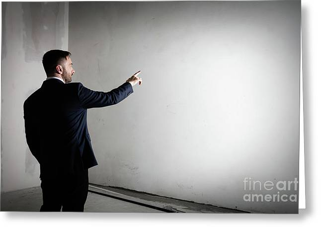 Businessman In An Open Empty Space Indoors Pointing His Finger At The Wall. Greeting Card