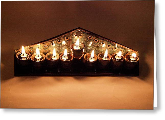 Ceramic Chanukkiah Lit With Eight Lights And One Lighter, The Shamash, Viewed From The Top Greeting Card by Yoel Koskas