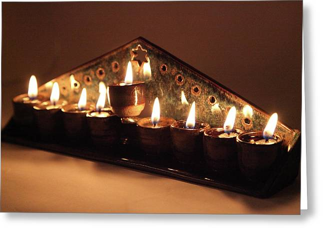 Ceramic Chanukkiah Lit With Eight Lights And One Lighter, The Shamash, Viewed On The Side Greeting Card by Yoel Koskas