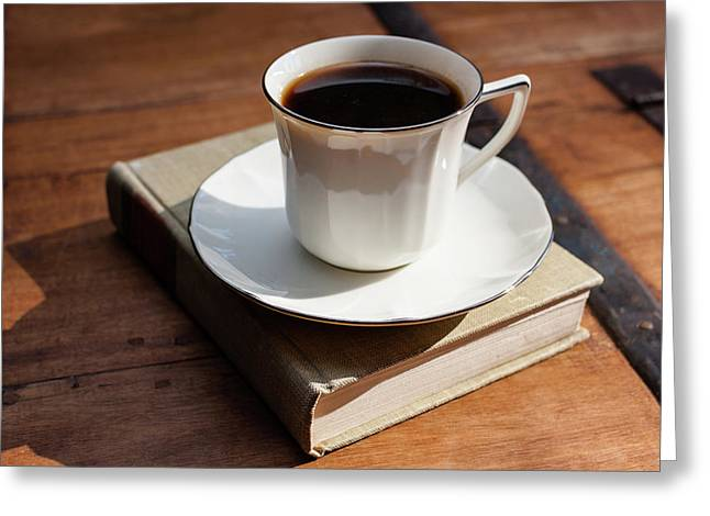 Cup Of Coffee Upon A Closed Book On Wooden Table Greeting Card by Bradley Hebdon
