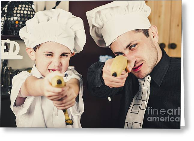 Dad And Son Cooks Shooting With Bananas In Kitchen Greeting Card