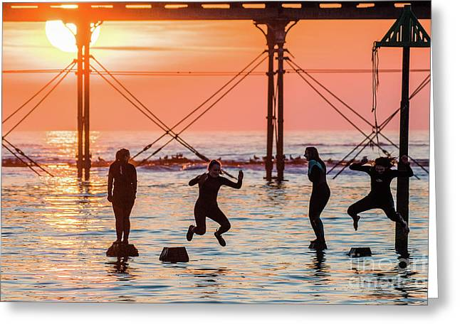Four Girls Jumping Into The Sea At Sunset Greeting Card