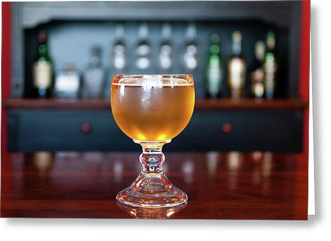 Goblet Of Refreshing Golden Beer On Shiny Dining Table Greeting Card by Bradley Hebdon