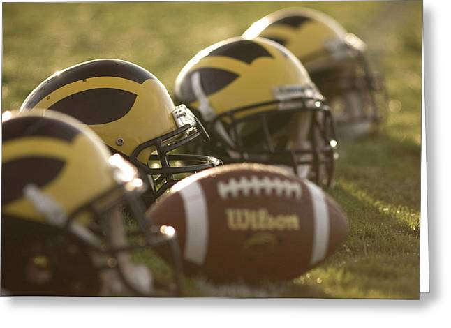 Greeting Card featuring the photograph Helmets And A Football On The Field At Dawn by Michigan Helmet