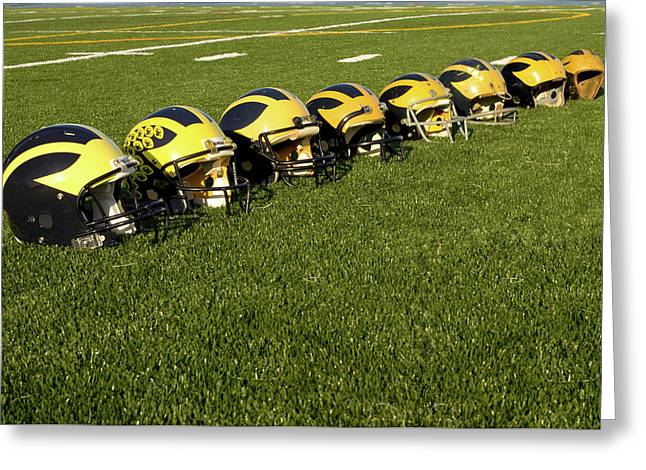 Greeting Card featuring the photograph Helmets Of Different Eras On The Field by Michigan Helmet