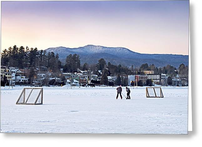 Kids Playing Hockey On Mirror Lake With Lake Placid Village Shown In The Background At Sunset  Greeting Card by Brendan Reals