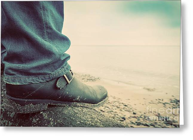 Man In Jeans And Elegant Shoes Standing On Fallen Tree On Wild Beach Looking At Sea Greeting Card