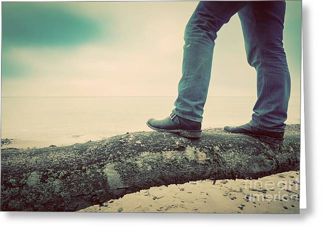 Man In Jeans And Elegant Shoes Standing On Fallen Tree On Wild Beach Looking At Sea. Vintage Greeting Card