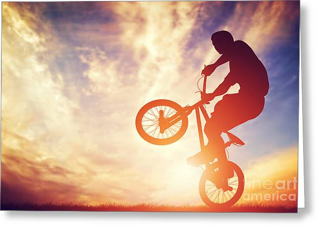 Man Riding A Bmx Bike Performing A Trick Against Sunset Sky Greeting Card