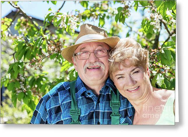 Mature Couple Embracing Time Together In The Garden. Greeting Card