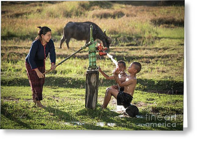 Greeting Card featuring the photograph Mother Her Sons Shower Outdoor From Groundwater Pump. by Tosporn Preede
