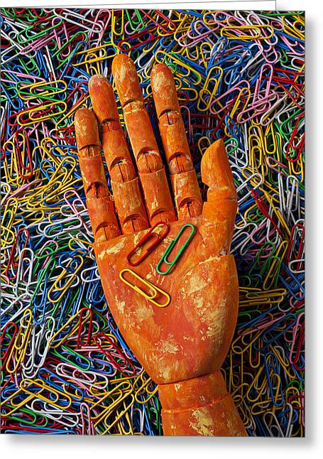 Supply Greeting Cards - Orange wooden hand holding paperclips Greeting Card by Garry Gay