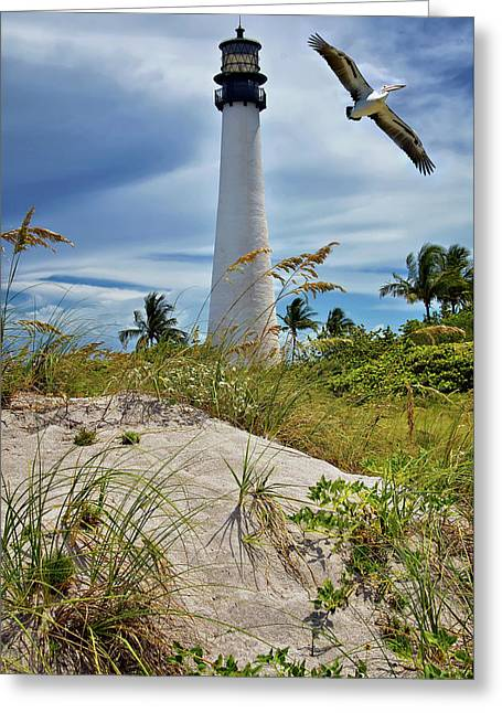Greeting Card featuring the photograph Pelican Flying Over Cape Florida Lighthouse by Justin Kelefas