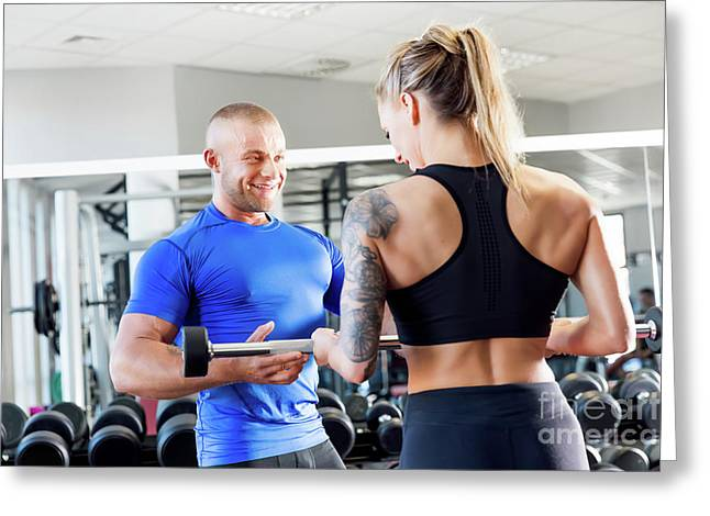 Personal Trainer Assisting While Exercises At The Gym. Greeting Card