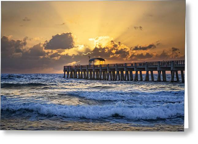 Rays Over The Pier Greeting Card by Debra and Dave Vanderlaan