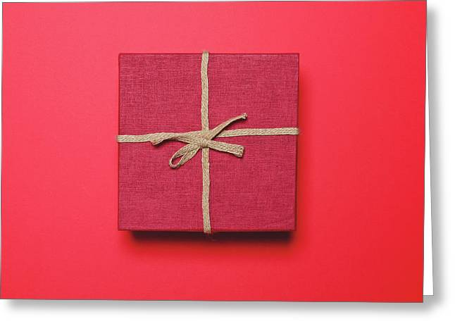 Red Gift Box With Rope Bow On Red Background - Minimal Design Greeting Card