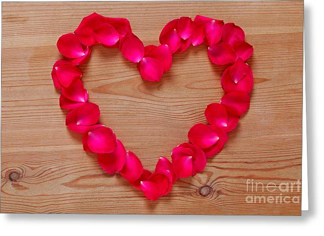 Red Rose Petal Heart On Wooden Background. Greeting Card