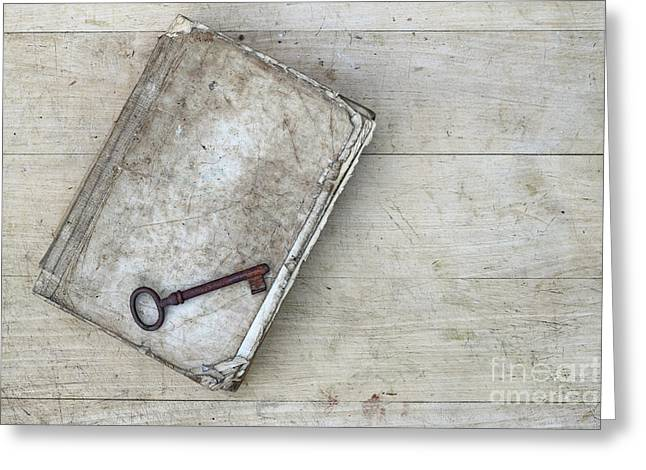 Greeting Card featuring the photograph Rusty Key On The Old Tattered Book by Michal Boubin