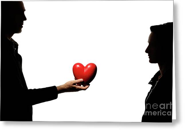 Silhouette Of Couple Standing Face To Face Man Holding Heartshaped Object Greeting Card by Sami Sarkis